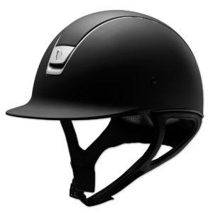 Un casco de equitación de policarbonato, con ventilación y con pintura negra anti rasguños.-