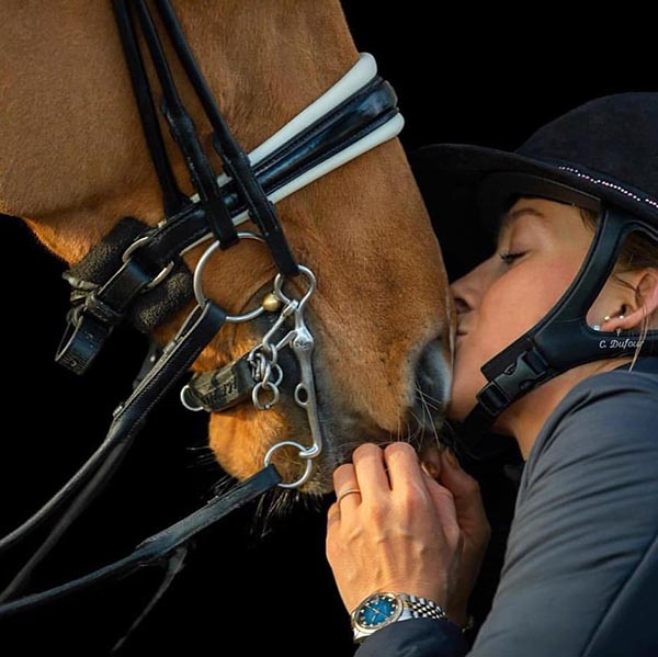 Catherine Dufour dando un beso a un caballo marrón