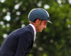 Un jinete risueño vestido con traje y un casco de equitación. Está en un bosque