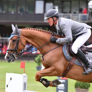 Ludger Beerbaum en un salto junto a su caballo marrón. Lleva unos guantes de equitación Roeckl y una americana gris.