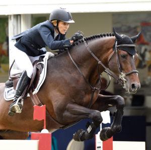 Meredith Michaels en un salto junto a su caballo marrón oscuro. Lleva unos guantes de equitación Roeckl y una americana azul marino.