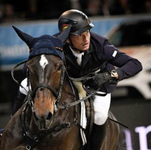 Michael Jung en una competición con su caballo oscuro. Lleva unos guantes de equitación Roeckl.