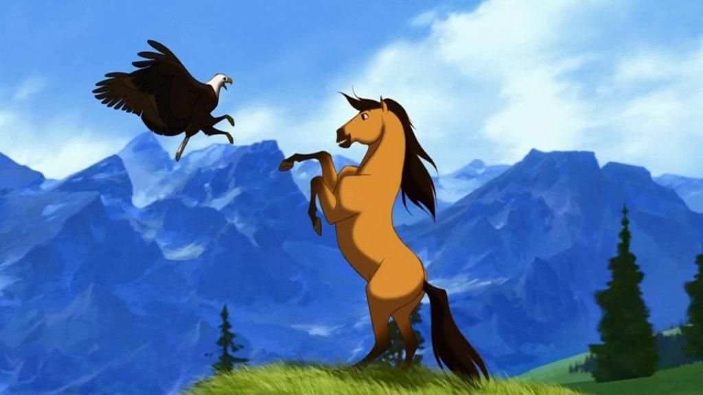 Spirit el caballo encima de sus dos patas jugando con un águila en un paisaje montañoso.