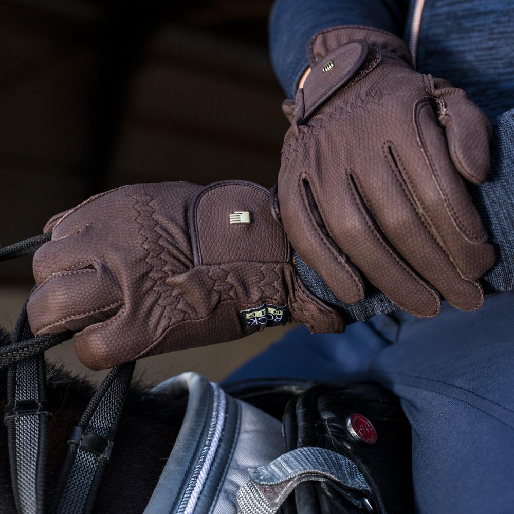 Un jinete en la silla de montar con unos guantes de equitación roeckl color marrón.