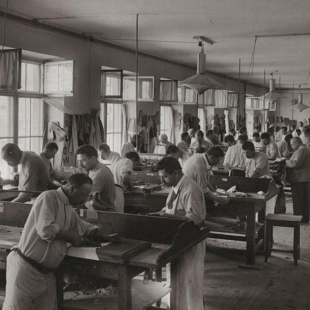 Una foto en blanco y negro del taller Roeckl en Austria. Los trabajadores estan creando guantes de equitación y otros deportes.