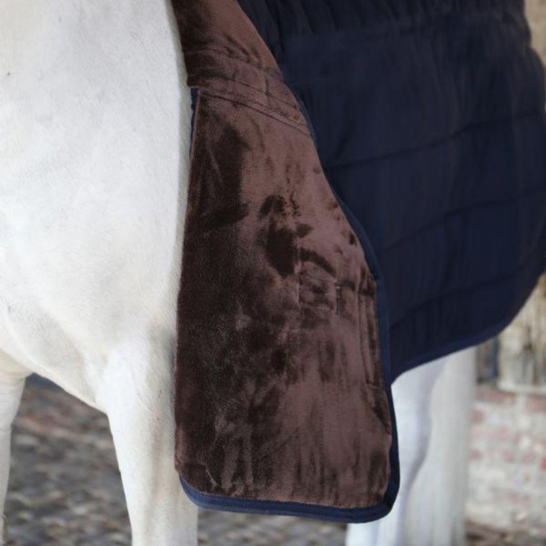 Un bajo mantas con pelo de color marrón en un caballo blanco. Es un material muy útil para proteger de rozaduras la piel del caballo.